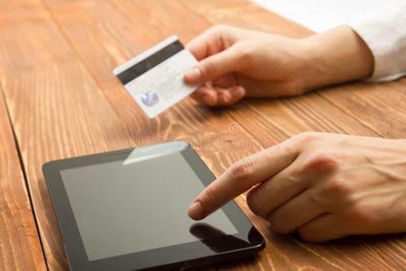 Mãos que guardam números de datilografia do cartão de crédito no PC da tabuleta que faz a pagamento em linha em casa a tabela de  fotografia de stock royalty free