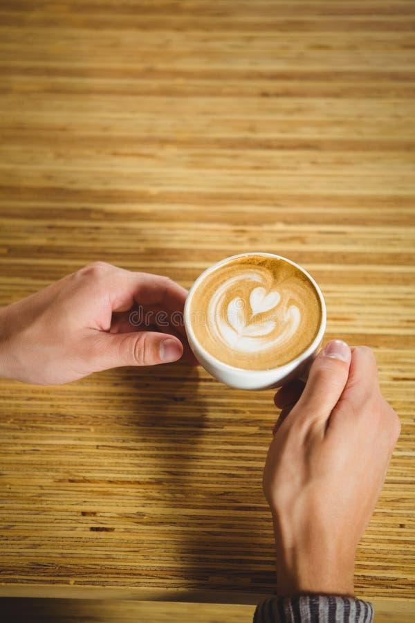 Mãos que guardam o cappuccino com arte do café fotografia de stock