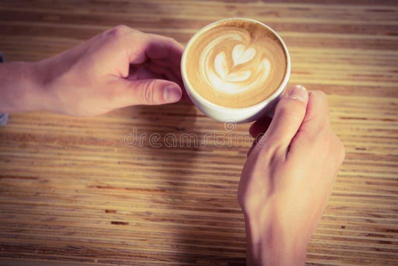 Mãos que guardam o cappuccino com arte do café fotos de stock