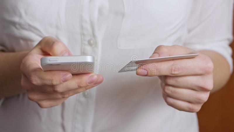 Mãos que guardam o cartão de crédito e que usam o telefone esperto móvel fotografia de stock