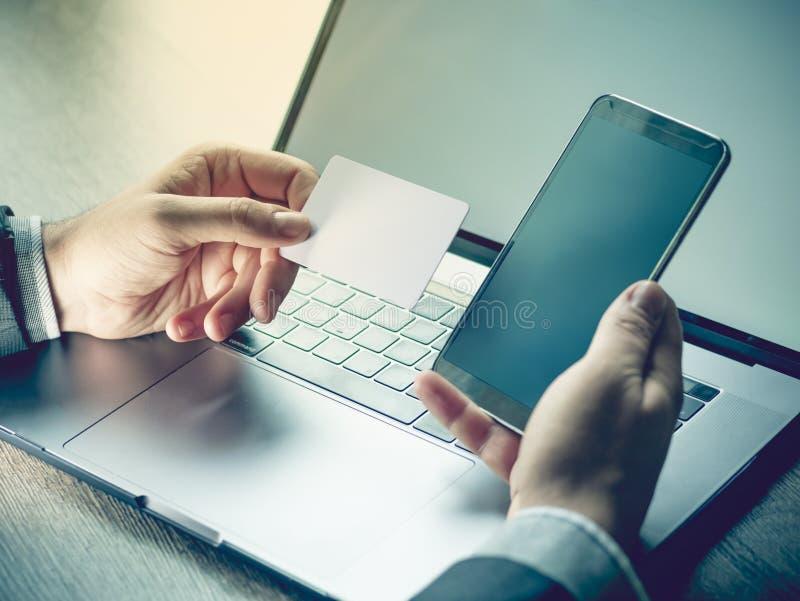 Mãos que guardam o cartão de crédito, telefone celular e usando o portátil Compra em linha, conceito do registro do curso Foco se foto de stock