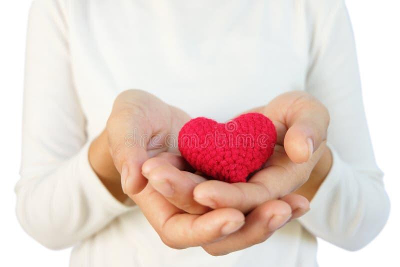 Mãos que guardam o coração, conceito do seguro do amor e da família, dia do coração do mundo, povos e conceito vermelhos da cardi imagens de stock royalty free