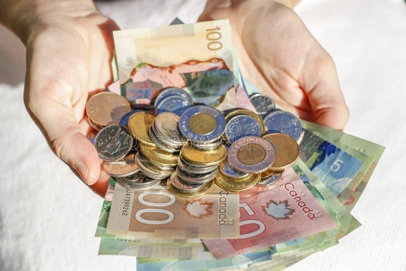 Mãos que guardam o dinheiro e contas canadenses fotografia de stock royalty free