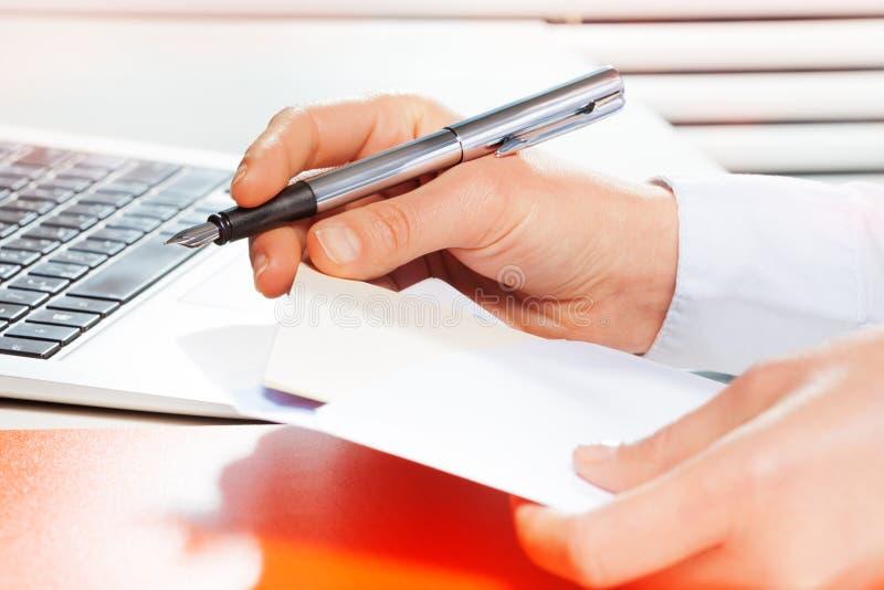 Mãos que guardam o envelope aberto com cópia-espaço imagens de stock