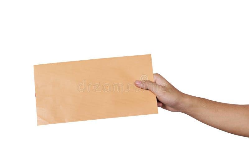 Mãos que guardam o envelope marrom imagem de stock