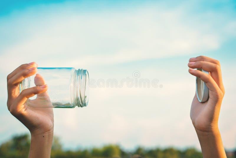 Mãos que guardam o frasco de vidro para manter o ar fresco imagens de stock