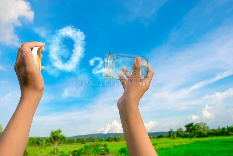 Mãos que guardam o frasco de vidro para manter o ar fresco, palavra da nuvem O2 com um céu azul no fundo imagens de stock royalty free