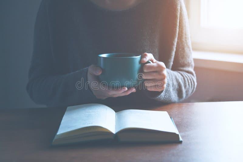Mãos que guardam o livro e que leem com café imagens de stock