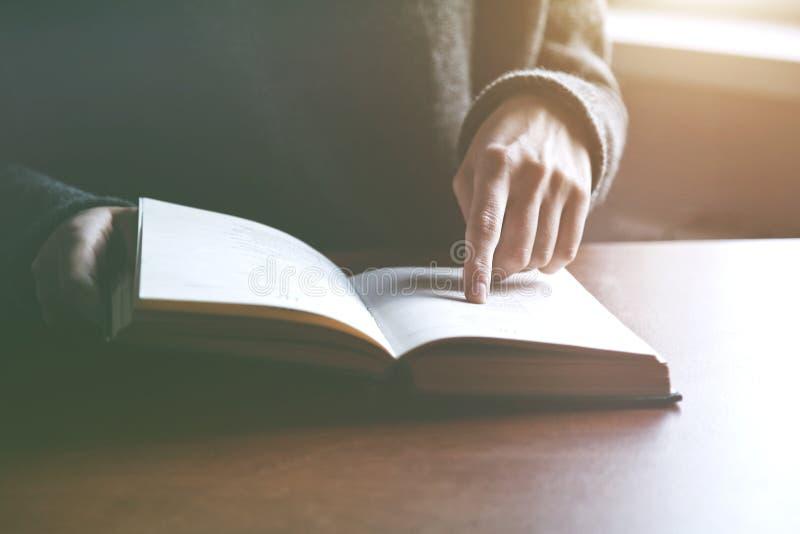 Mãos que guardam o livro e a leitura fotografia de stock