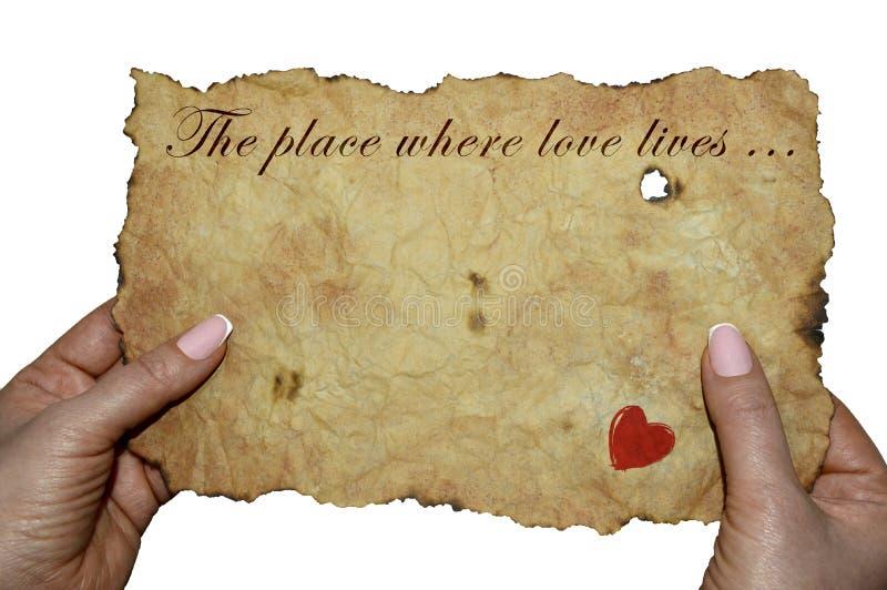 Mãos que guardam o pergaminho velho com a inscrição 'o lugar onde vidas do amor ' imagens de stock royalty free