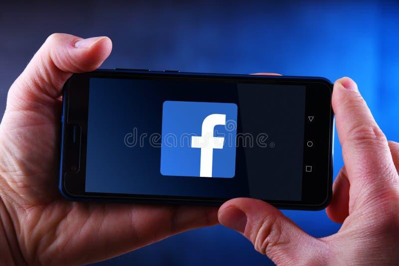 Mãos que guardam o smartphone que indica o logotipo de Facebook fotografia de stock royalty free