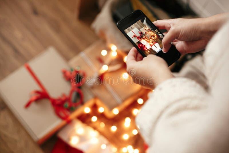 Mãos que guardam o telefone e que tomam a foto de caixas de presente do Natal, chapéu de Santa, luzes da iluminação no fundo de m imagem de stock