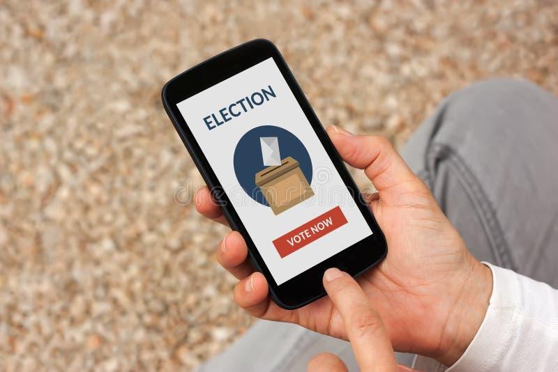 Mãos que guardam o telefone esperto com conceito de votação em linha na tela imagem de stock