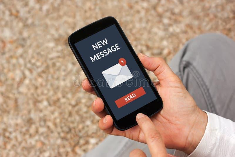 Mãos que guardam o telefone esperto com conceito novo da mensagem na tela fotos de stock