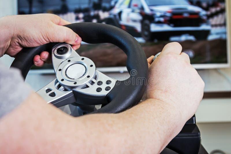 Mãos que guardam o volante do console do jogo imagens de stock