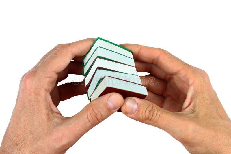 Mãos que guardam os livros diminutos pequenos, isolados no branco imagem de stock royalty free