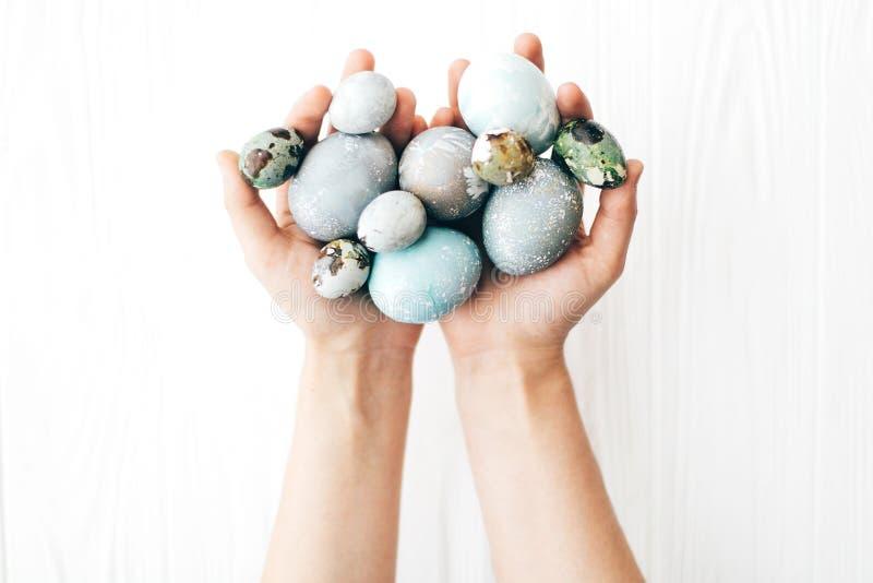Mãos que guardam ovos da páscoa à moda no fundo de madeira branco Ovos da páscoa coloridos modernos pintados com a tintura natura imagens de stock