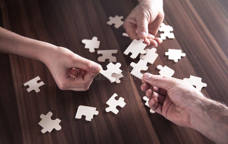 Mãos que guardam a parte do enigma de serra de vaivém Solução, sucesso, trabalhos de equipe imagem de stock royalty free