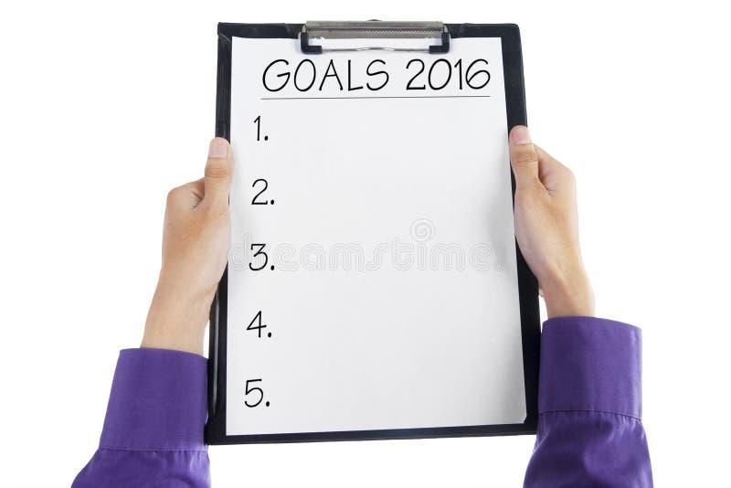 Mãos que guardam a prancheta para fazer objetivos de negócios em 2016 fotos de stock