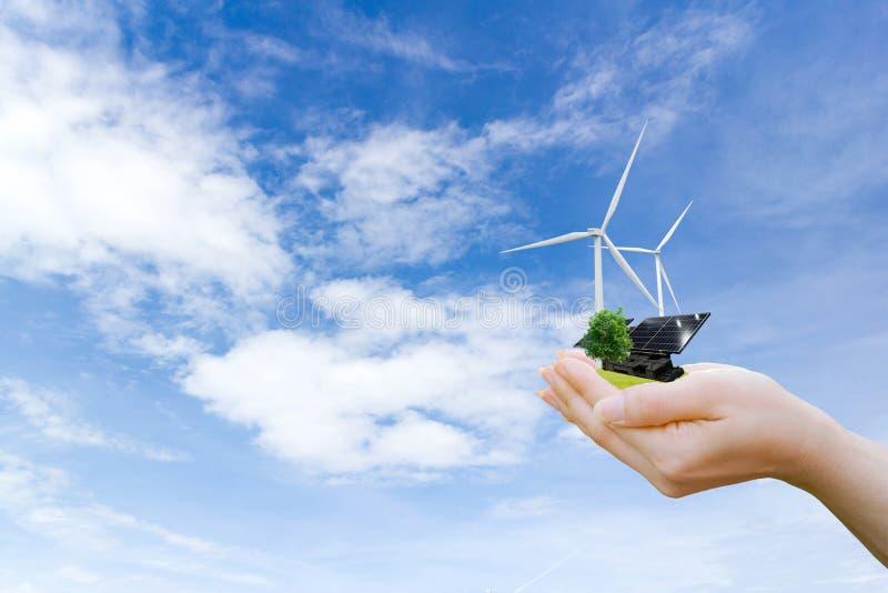 Mãos que guardam a turbina eólica limpa e a célula solar da energia elétrica da árvore o futuro imagem de stock