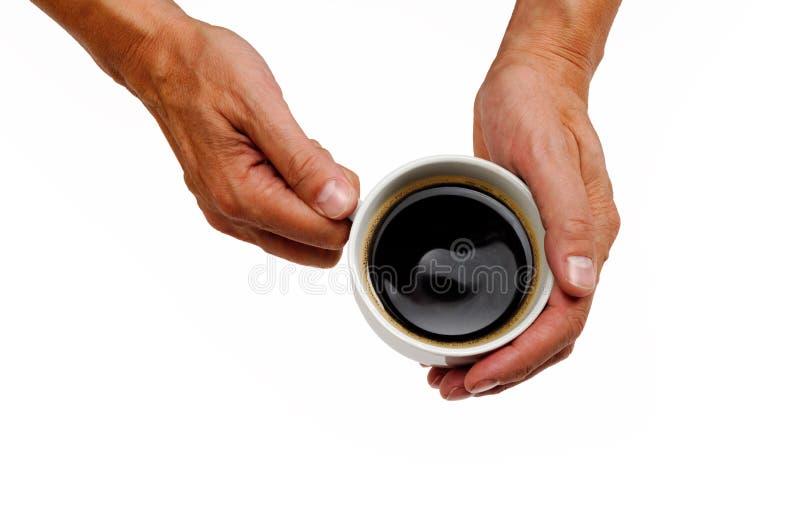 Mãos que guardam um copo de café imagens de stock