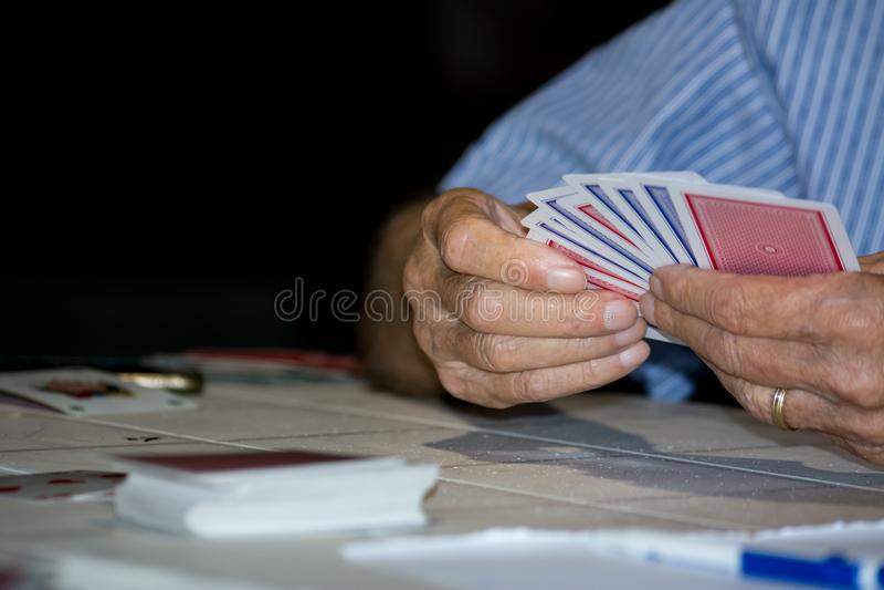 Mãos que guardam um grupo de cartões de Ramino durante um fósforo imagem de stock