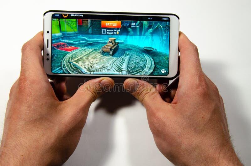 Mãos que guardam um smartphone em que o jogo, mundo gameplay de Gameplay do raio dos tanques imagem de stock royalty free