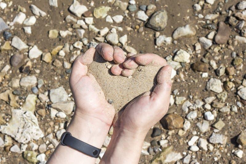 Mãos que guardam uma areia nas palmas do coração, o conceito de vida que corre para fora como a areia através dos dedos fotografia de stock