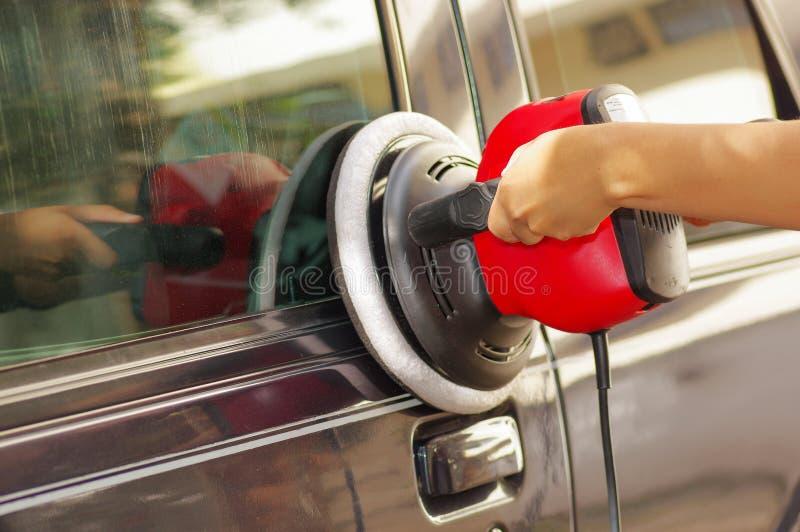 Mãos que guardam uma máquina do amortecedor do poder que limpa um carro fotos de stock royalty free