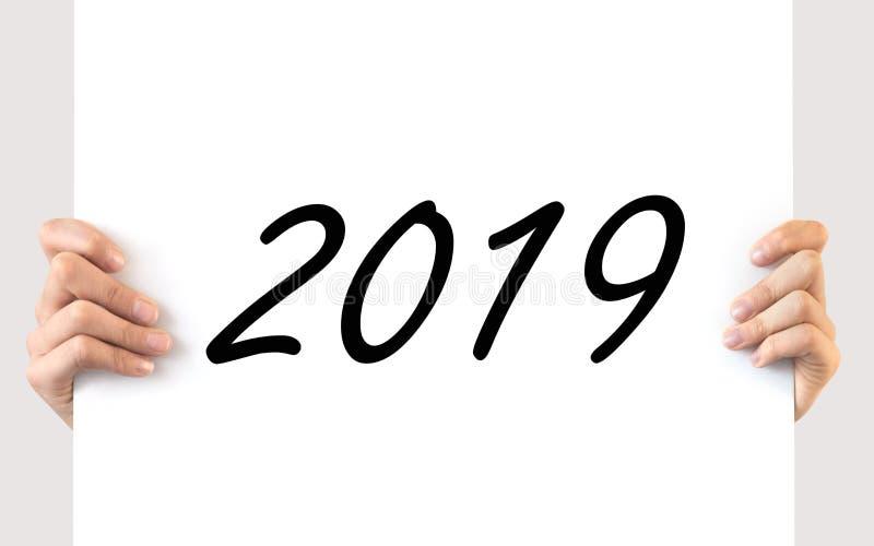 Mãos que guardam uma placa branca 2019 imagem de stock