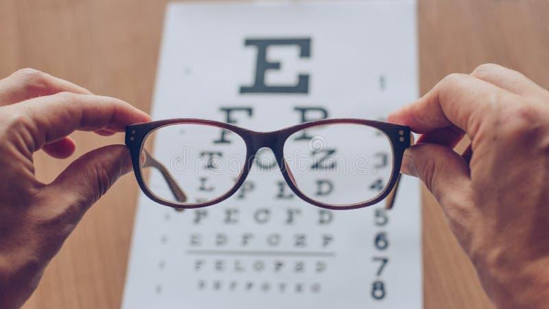 Mãos que guardam vidros de vista na frente da carta da vista do ótico Conceito do ótico da visão foto de stock royalty free