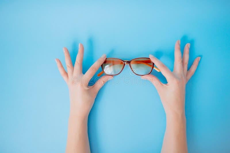 Mãos que guardam vidros no fundo azul fotografia de stock