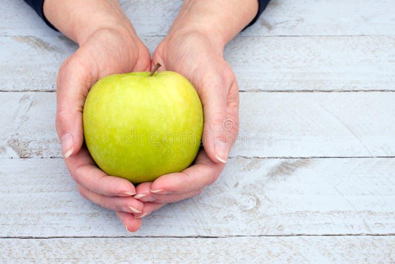 Mãos que guardaram a maçã imagem de stock