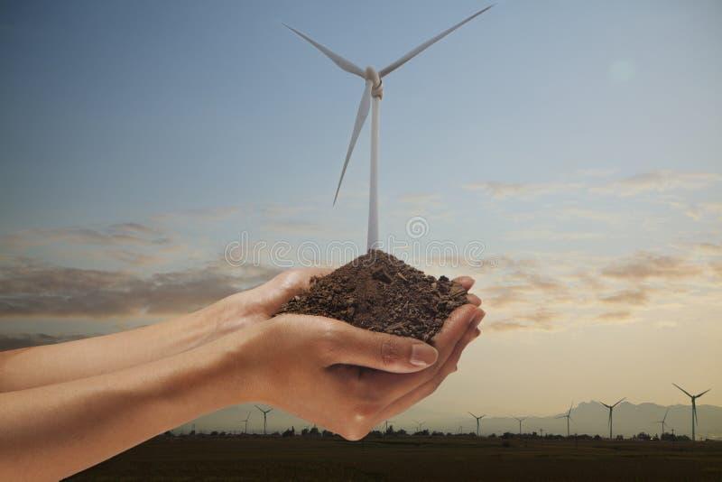 Mãos que guardaram o solo com uma turbina eólica que cresce para fora do meio imagens de stock royalty free