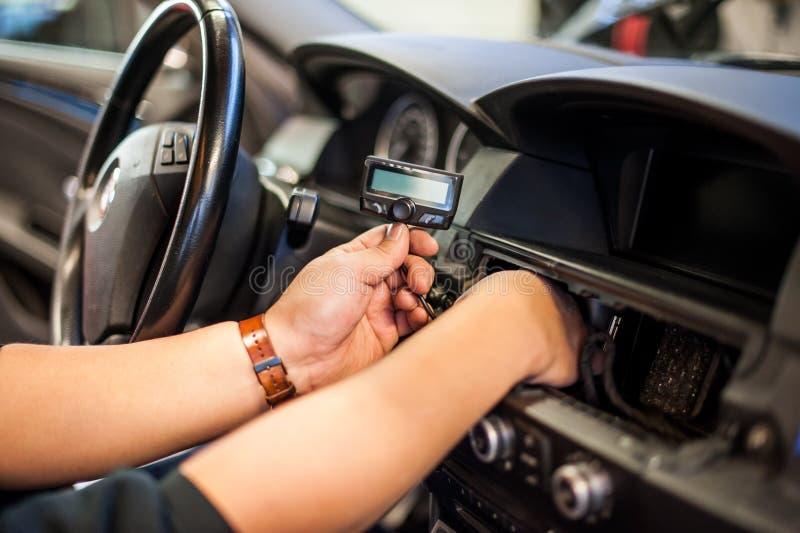 Mãos que instalam a exposição pequena no carro foto de stock royalty free