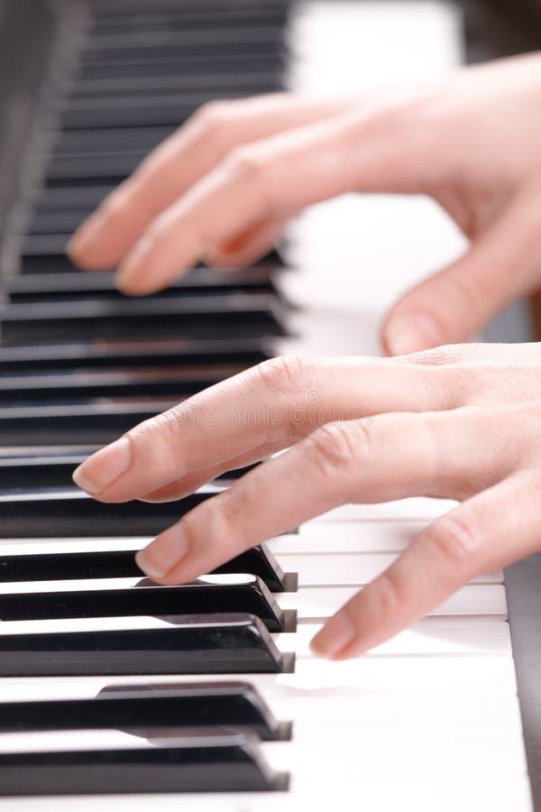 Mãos que jogam a música no piano fotografia de stock royalty free