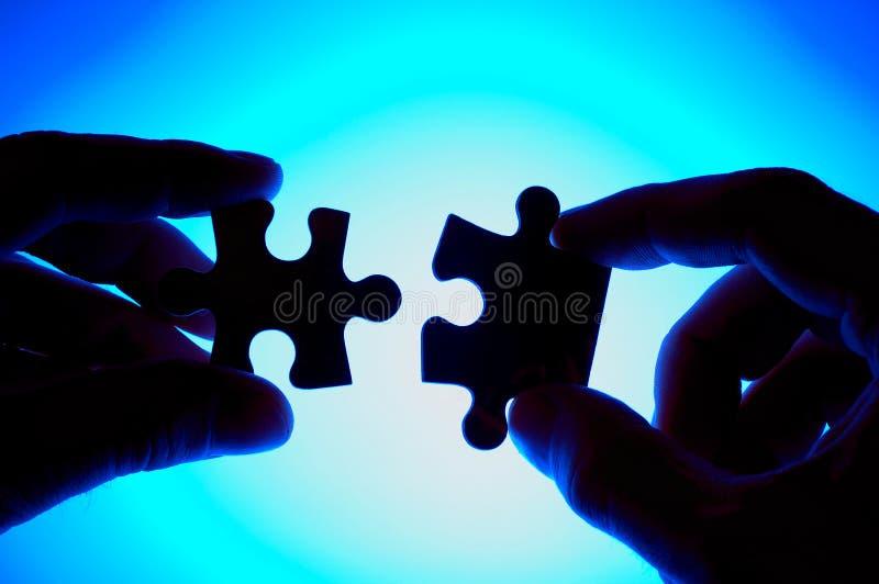 Mãos que juntam-se a duas partes do enigma. imagem de stock royalty free