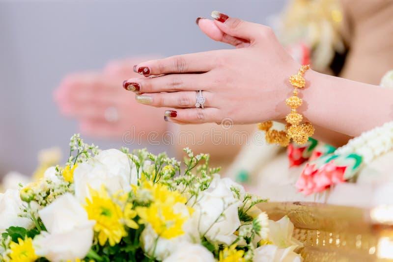 Mãos que levam água de bênção para as bandas da noiva, casamento tailandês fotos de stock