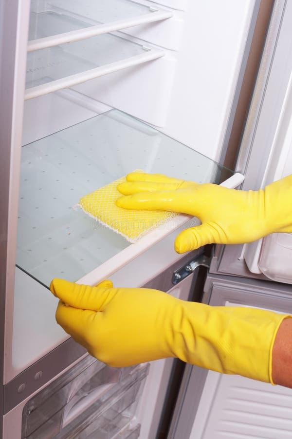 Mãos que limpam o refrigerador. foto de stock royalty free