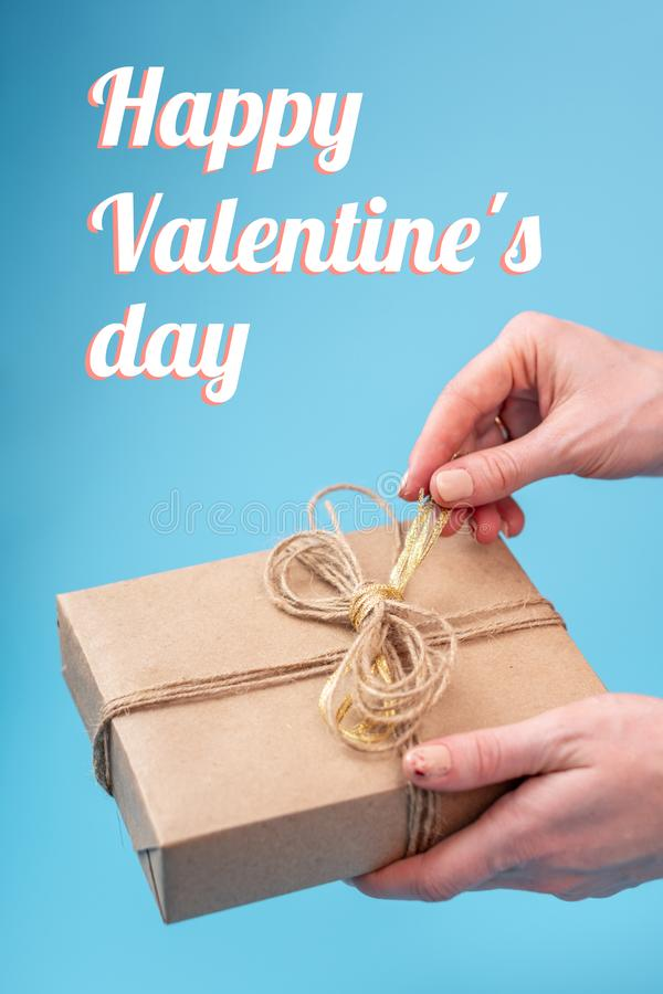 Mãos que mantêm a caixa de presente embalada no papel de embalagem no fundo azul O dia de Valentim feliz do cartão vertical do fe foto de stock royalty free