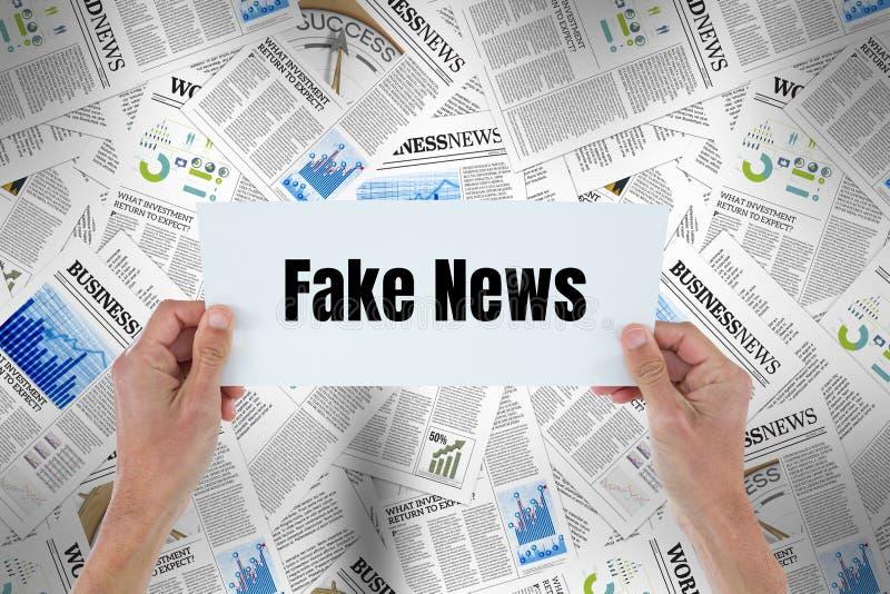 Mãos que mantêm o cartão com notícia falsificada contra os jornais 3d fotos de stock