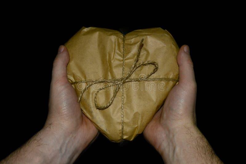Mãos que mantêm um presente coração-dado forma envolvido no papel imagem de stock