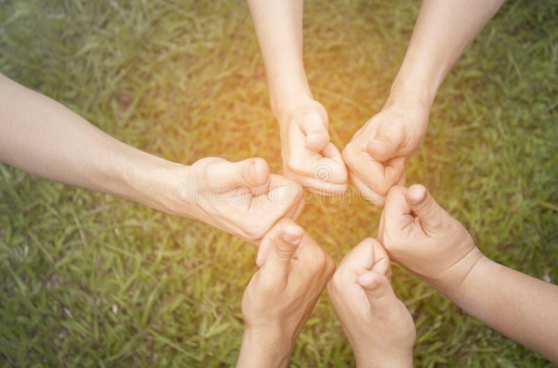 Mãos que mostram os polegares acima sobre o fundo natural verde fotografia de stock royalty free