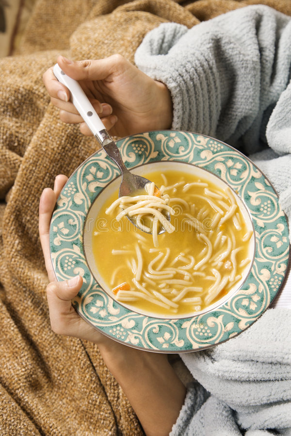 Mãos que prendem a bacia de sopa de macarronete da galinha. imagem de stock royalty free