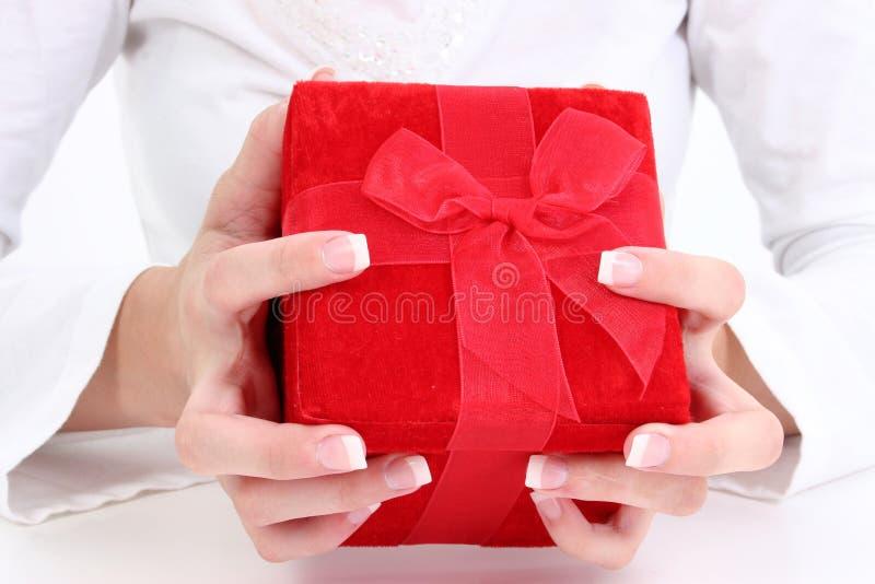 Mãos que prendem a caixa de presente vermelha de veludo foto de stock