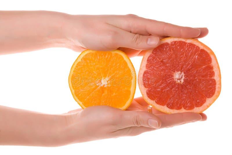 Mãos que prendem a laranja e a pamplumossa cortadas fotografia de stock royalty free