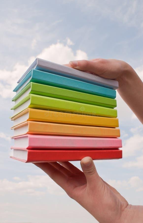 Mãos que prendem livros duros da tampa da cor fotografia de stock