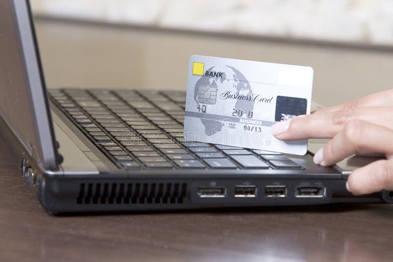 Mãos que prendem o cartão de crédito, compra em linha fotos de stock royalty free