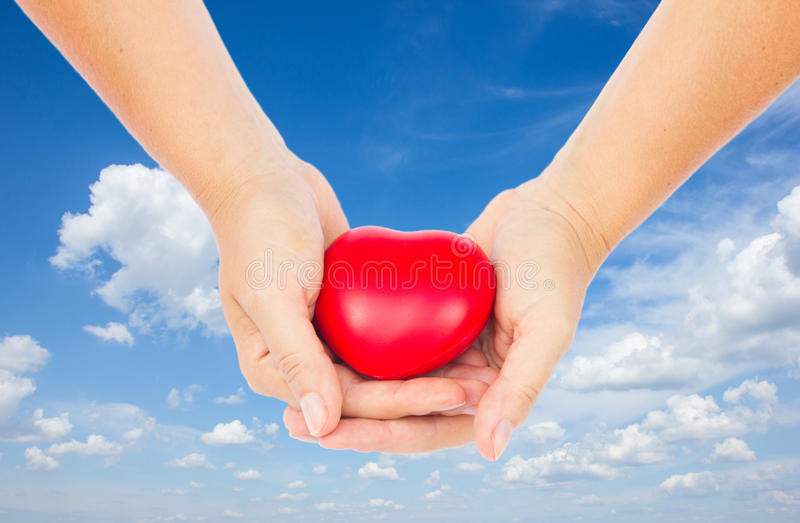Mãos que prendem o coração vermelho foto de stock
