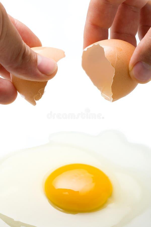 Mãos que quebram o ovo imagem de stock